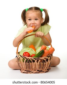 Cute little girl eats carrot while sitting on the floor with basket full of vegetables, isolated over white
