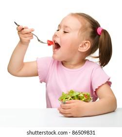 Cute little girl eats vegetable salad using fork, isolated over white