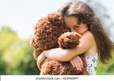 Cute little girl embracing her new teddy bear and looking at camera. Portrait of lovely female child with her peluche outdoor. Little girl playing with her doll.