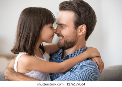 Cute little girl embracing touching noses with happy single dad, kid daughter and father having fun hugging bonding feeling love connection enjoy time together, warm relationships of daddy and child