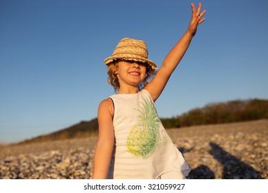 Cute little girl emotional outdoor portrait in warm light of sunset