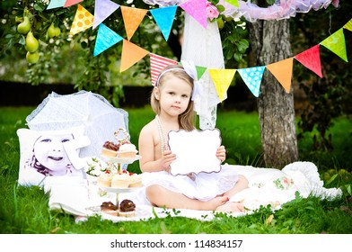 Cute little girl with with empty board with space for text on party background