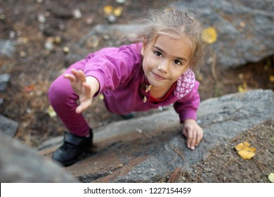 A cute little girl engaged in the sports of rock climbing on the rock, outdoor extreme sport and active lifestyle, natural rock mountains