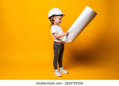 Cute little girl engineer with helmet holding bluepring isolated on yellow background