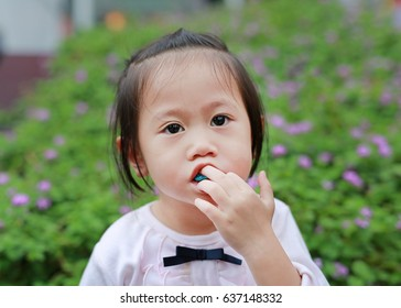 Cute little girl enjoy eating bubble gum.