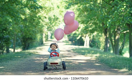 cute little girl enjoy a ride on her pedal car - Kid leisure on summer day