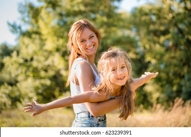 Cute little girl enjoying airplane ride in arms of her elder sister.