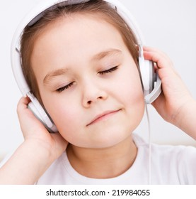 Cute little girl is enjoying music using headphones and closed her eyes