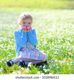 Cute little girl enjoying traditional Easter egg hunt in blooming spring garden. Child searching for colorful eggs in snow drop flower meadow. Kid having fun on warm sunny day outdoors.