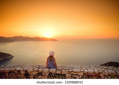 Cute little girl enjoying the view of picturesque jagged coastline of Kefalonia on summer sunset. Cephalonia, Ionian islands, Greece.