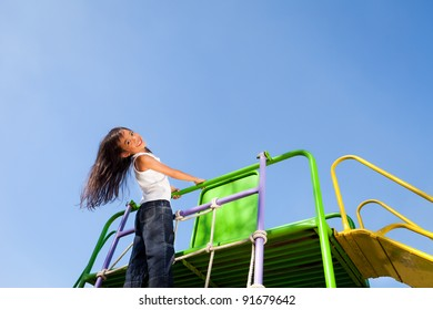 Cute little girl enjoys playing in a children playground