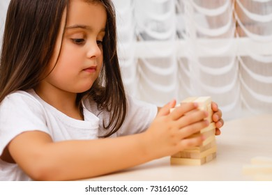 cute little girl excites with wooden block game jenga at home selective focus