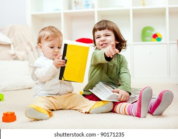 Cute little girl expressing discontent and her baby bother reading