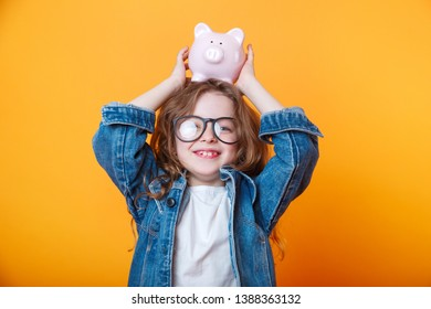 Cute little girl in eyeglasses shaking piggy box on orange background