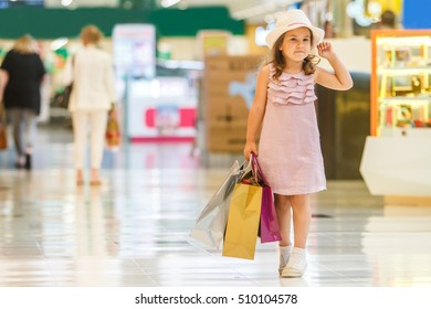 cute little girl in fashionable hat on shopping. portrait of a kid with shopping bags. child in shopping mall having fun. shopping. girl. fashion