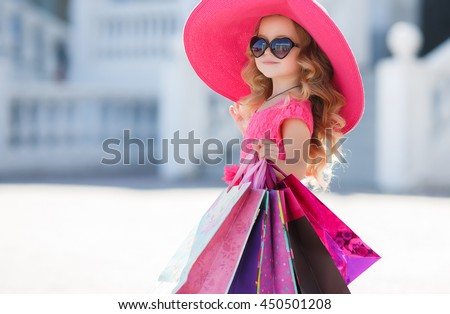 2a8d8c05d03be cute little girl in fashionable hat on shopping. portrait of a kid with  shopping bags