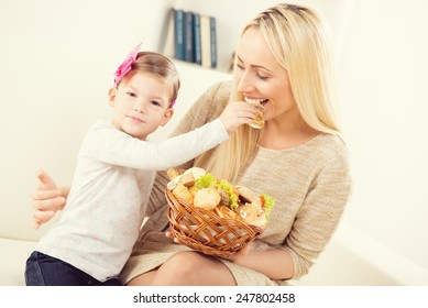Cute little girl feeding pretty mom with pastries from woven baskets.