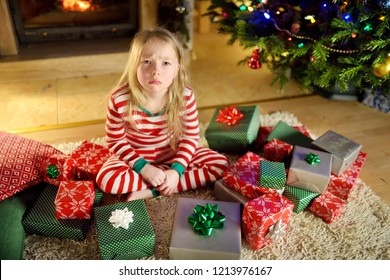 Cute little girl feeling unhappy with her Christmas gifts. Child sitting by a fireplace in a cozy dark living room on Xmas eve. Too many presents for Christmas.