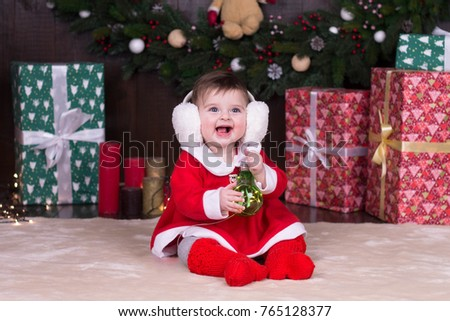 422cc8e94 Cute little girl in festive costume and fluffy headphones playing with  lightbulb toy, baby celebrates
