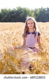 Cute little girl in field of wheat sunny summer day. Blonde girl smiling and looking at the camera. Happy smiling child outside.