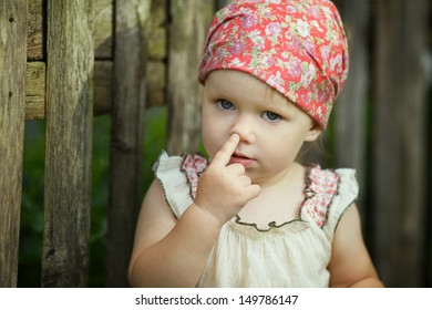 Cute little girl with finger in her nose
