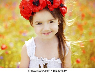 Cute little girl with flower garland in the poppy field