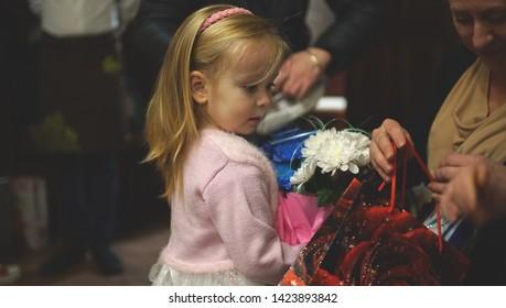 Cute little girl with flowers watching her mom on the birhday party