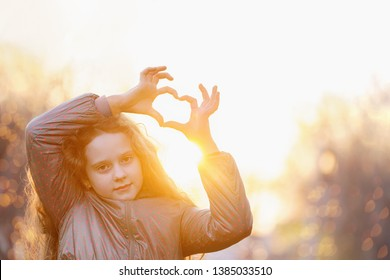 Cute little girl  girl folded her hands a heart shape in spring outdoors. Healthy, lifestyle, earth hour, ecology concept.