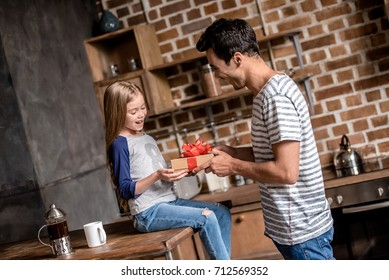 Cute little girl is getting a gift box from her handsome dad, both are smiling while spending time together in kitchen