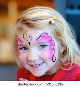 Cute little girl getting her face painted like a butterfly by face painting artist. Kids animation at the party.