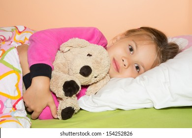 Cute little girl is getting ready to get to bed and hugging a plush dog