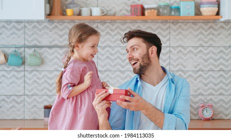 Cute little girl giving a gift to dad for a holiday in the living room. One parent with a child at home
