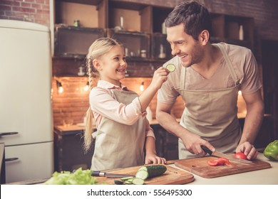 Cute little girl is giving her handsome dad a slice of cucumber and smiling while he is cutting vegetables