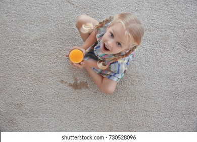 Cute little girl with glass of juice sitting on carpet near wet spot