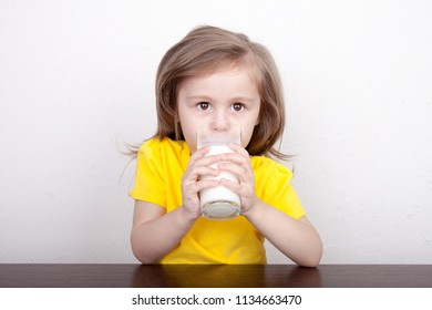 Cute little girl with a glass of milk on a light background