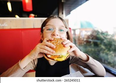 Cute little  girl in glasses and school uniform  eating a hamburger and potatoes in the restaurant