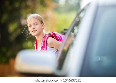 Cute little girl going home from school, looking well before crossing the street, trying not to get git by a car