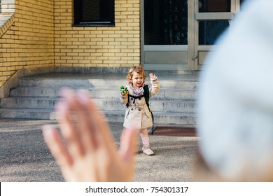 Cute little girl going to school and waving to her mother