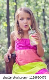 Cute little girl goofing around and drinking lemonade