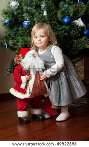 7b54f3859 Cute little girl in gray dress with toy Santa Claus under the Christmas tree