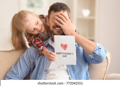 Cute little girl greeting her dad with Father's Day at home