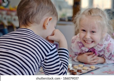 Cute little girl grinning mischievously at her brother as they sit at a table together playing a game of checkers or draughts