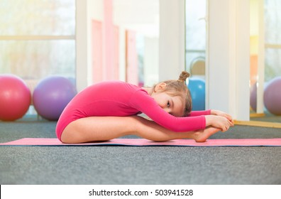 Cute little girl gymnast in gym. Sport, training, fitness, yoga, active lifestyle concept