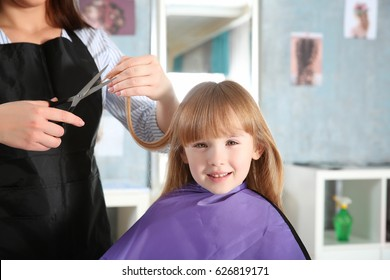 Cute little girl in hairdressing salon