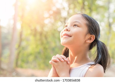 cute little girl hands praying to god with the bible in the morning on nature background.  little asian girl hand praying for thank god. copy space. spirituality and religion faith hope concept.