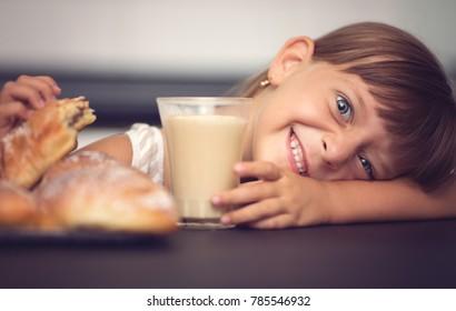 Cute little girl has breakfast.
