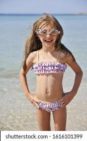 Cute little girl has fun on the beach. Summertime concept.