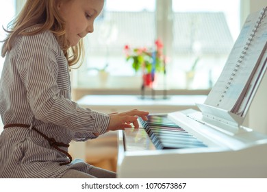 Cute little girl has training course with piano