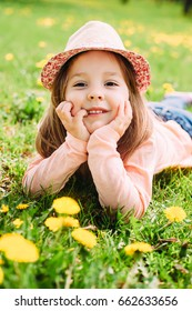 Cute little girl with hat lying on the grass