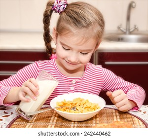 Cute little girl having breakfast cereals with milk in the kitchen